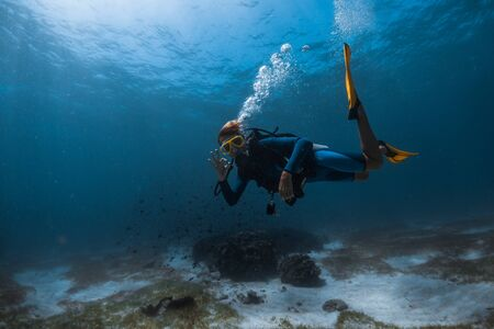 Woman scuba diver swims underwater over the sea bottom exhales the air and shows the OK diving sign