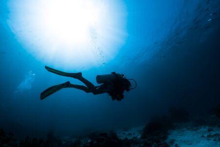 Silhouette des Tauchers, der allein in der Tiefe schwimmt Standard-Bild