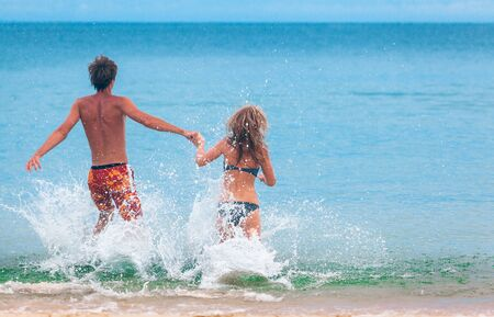 Happy couple runs into the sea with splashes