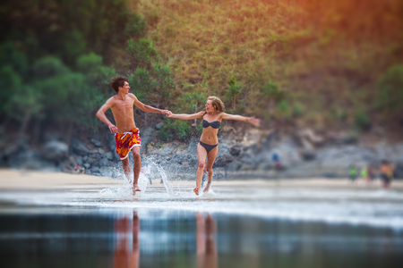 Happy couple runs along the beach with splashes