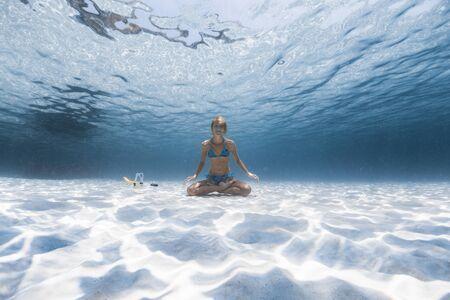 Une dame yogi mince est assise sur le fond sablonneux de la mer dans la pose détendue de Lotus, sourit et regarde la caméra