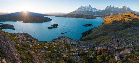 Panorama of Torres del Paine National Park with snow capped mountains (Cordillera Paine) and blue lake of Pehoe as seen from the Mirador Condor during sunset. Chilean Patagonia