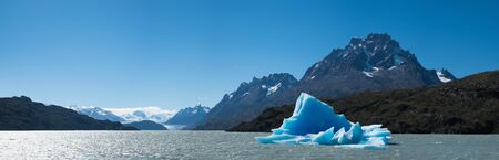 Panorama of the Grey with the blue iceberg (bergy bit  floating in it. Torres del Paine National Park, Chile