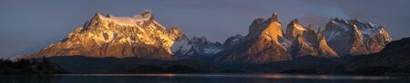 Panorama of Torres del Paine National Park with snow capped mountains (Cordillera Paine) and calm lake of Pehoe at sunrise. Chile Stock fotó