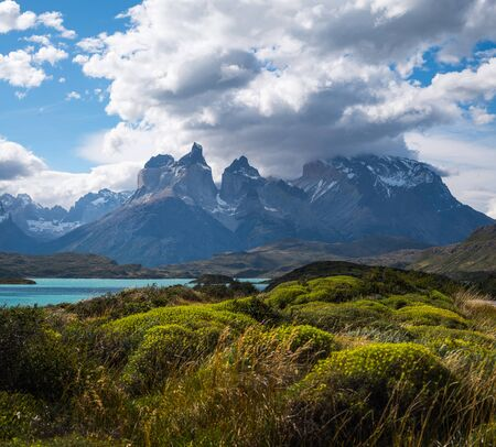 Torres del Paine National Park with snow capped mountains (Cordillera Paine) covered in the clouds and lush green vegetation on the foreground. Chile Stock fotó