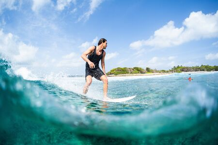 HIMMAFUSHI  MALDIVES - MARCH 08, 2019: Young surfer rides the ocean wave on the Sultans surf spot in Maldives