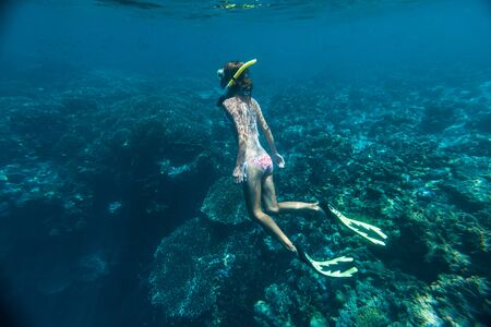 Girl snorkeling in the tropical sea over the coral reef