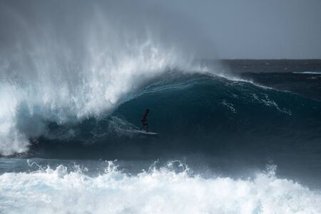Confident surfer rides giant barreling wave at the famous Banzai Pipeline surf spot located on the North Shore of Oahu in Hawaii