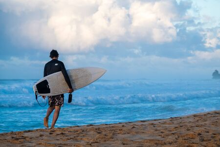 OAHU  USA - NOVEMBER 13, 2019: Surfer walks along the beach with his surfboard. Seven Mile Miracle on The North Shore of Oahu, Hawaii 報道画像