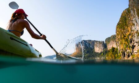 Young woman paddles kayak in the sea with splash and underwater view