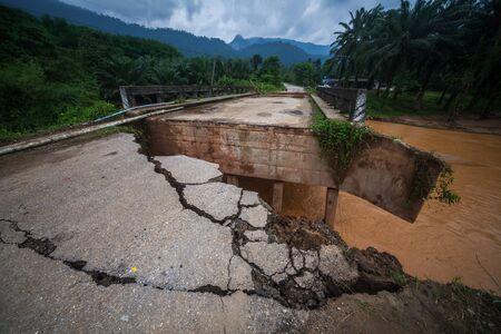 Damaged asphalt road and rapid dirty river flowing under the concrete bridge