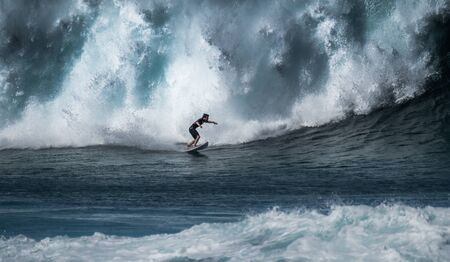 Surfer rides giant wave breaking at the famous Banzai Pipeline surf spot located on the North Shore of Oahu in Hawaii