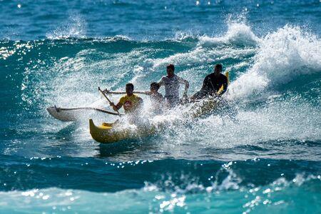 OAHU, HI / USA - NOVEMBER 17, 2018: Two fathers with kids surf canoe in Hawaiian waters Sajtókép