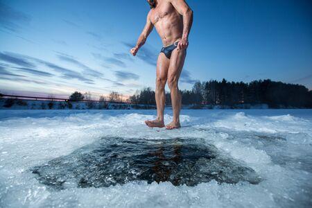 Il giovane con la barba sta a piedi nudi sul ghiaccio dopo aver nuotato nel lago d'inverno