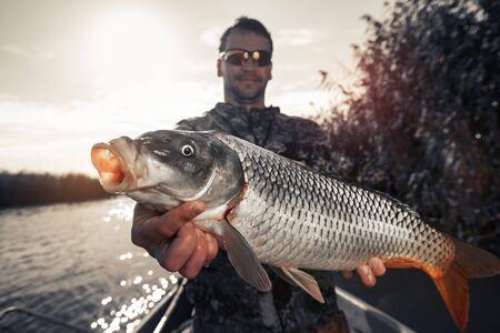Angler holds big Carp fish and smiles
