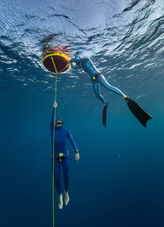 Der Freitaucher steigt entlang des Seils aus der Tiefe auf, während sich ein anderer Freitaucher auf der Boje entspannt