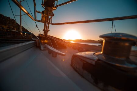 Bow of the sailing vessel with anchor chain at sunrise