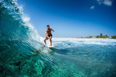 Surfer berijdt oceaangolf in tropen Stockfoto