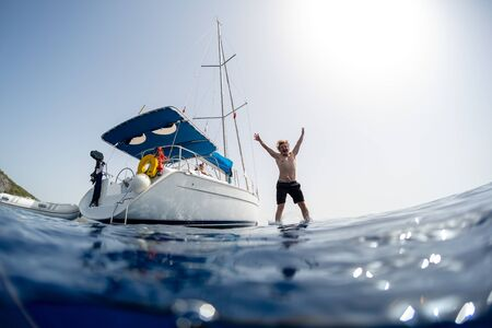 Young man jumps into the sea from the sail boat Imagens