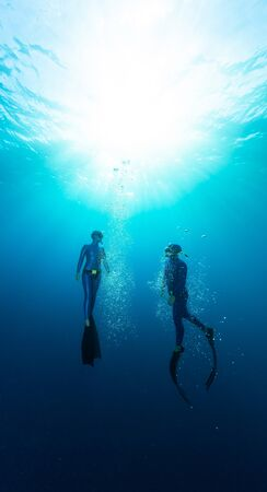 Two freedivers ascend from the depth surrounded by bubbles