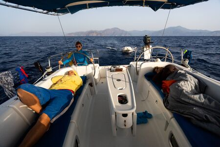 Young woman steers the boat while two men sleep in the cockpit