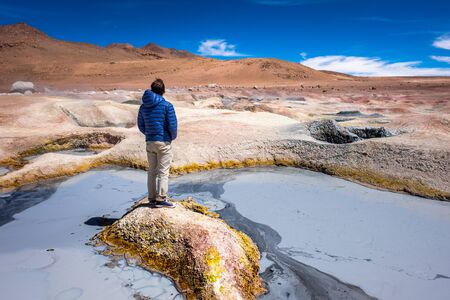 Young man stands on a tiny sulfur island with muddy lake around. Geothermal area named Sol de Manana in Bolivian Altiplano Imagens