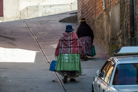 Two women in national dress walk up on the steep street in the city of La Paz in Bolivia Reklamní fotografie