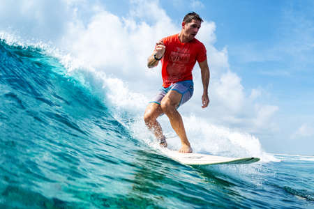 HURAA , MALDIVES MARCH 10, 2019: Hispanic young man surfs the wave on the Sultans surf spot in Maldives Editorial