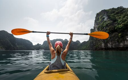 Woman sits in the yellow kayak holds the paddle and enjoys the Ha Long Bay view in Vietnam