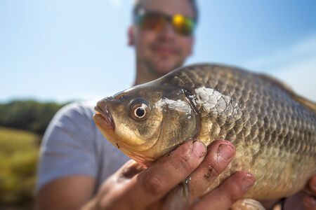 Young happy angler holds the fish (Carassius) and smiles with natural background