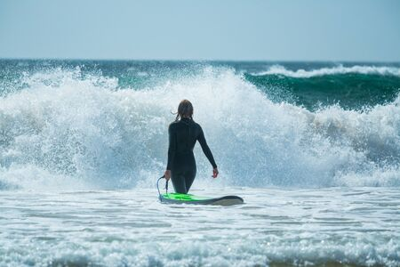 Young woman in black wetsuit holds surfboard and walks into the furious ocean with huge waves