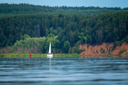 Sailing boat motoring on Kama river at calm windless day with steep coast and forest on the background. Russia