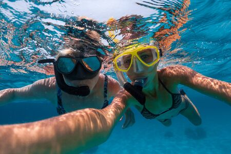 Young lady swims with her mom in the tropical sea and takes selfie