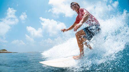 Un jeune homme de race blanche surfe sur la vague de l'océan et fait beaucoup d'éclaboussures dans l'appareil photo. Spot de surf des poules aux Maldives