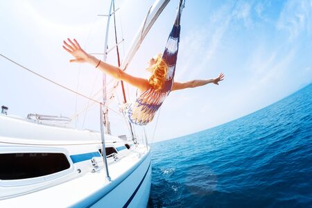 Young woman enjoys tropical sailing in the hammock set on the yacht
