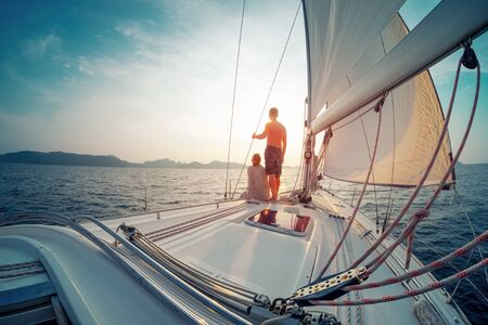 Young couple sailing in the tropical sea at sunset on their yacht