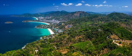 Aerial panorama of the coastline of the island of Phuket with tropical sandy beaches and green mountains. Thailand