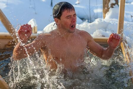 Young man haves bath in the icy water