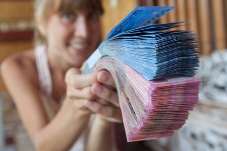 Happy young woman holds big pile of cash and holds it in front of the camera Standard-Bild