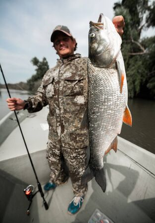 Angler stands in the boat and holds the trophy Asp fish