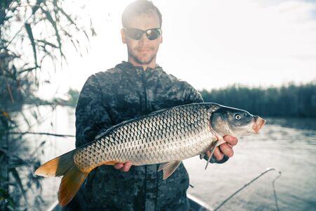 Fischer hält Karpfen und schaut in die Kamera Standard-Bild