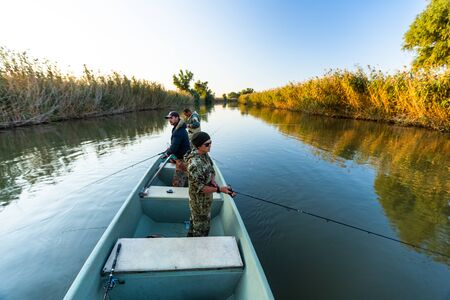 Anglers fishing from the boat on the calm river in Astrakhan Region in Russia. Astrakhan is a famous fishing destination Фото со стока