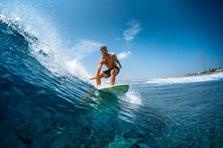 Young athletic surfer rides the wave in tropics with splashes. Jailbreaks surf spot in Maldives