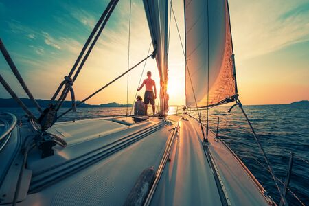 Young couple sailing on the boat at sunset Stockfoto