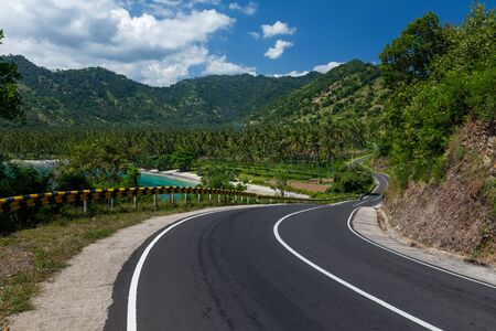 Scenic asphalt road along the coastline of the island of Lombok in Indonesia