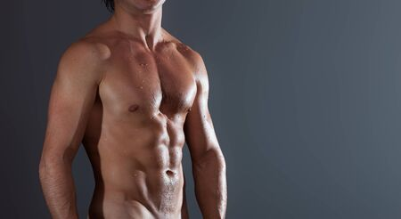 Young bodybuilder with naturally looking and wet body (bady has hairs and birthmarks) on a grey background