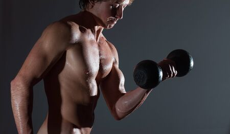 Young bodybuilder with naturally looking and wet body (body has hairs and birthmarks) holds dumbbell