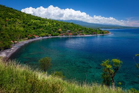 Green and hilly coastline of Bali island in the area of Amed village, Indonesia