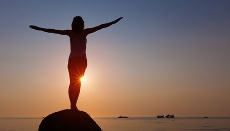 Woman stands on the rock with stretched hands and enjoys sunset Фото со стока