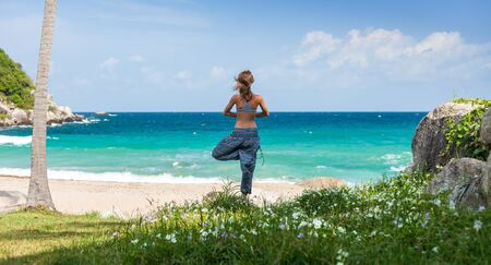 Young woman performs yoga exercises on a green lawn with sea on the background Standard-Bild